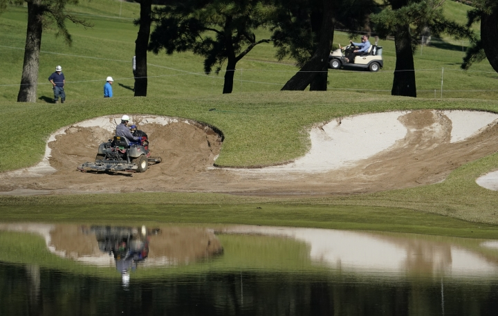 Grounds crew workers repair a bunker on the 10th hole before the start of the second round of the Zozo Championship PGA Tour at the Accordia Golf Narashino country club in Inzai, east of Tokyo, Japan, Saturday, Oct. 26, 2019. (AP Photo/Lee Jin-man)