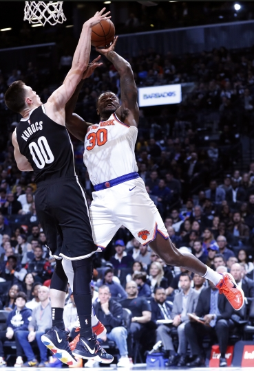 Brooklyn Nets forward Rodions Kurucs (00) defends against New York Knicks center Julius Randle (30) during the first half of an NBA basketball game, Friday, Oct. 25, 2019, in New York. (AP Photo/Kathy Willens)