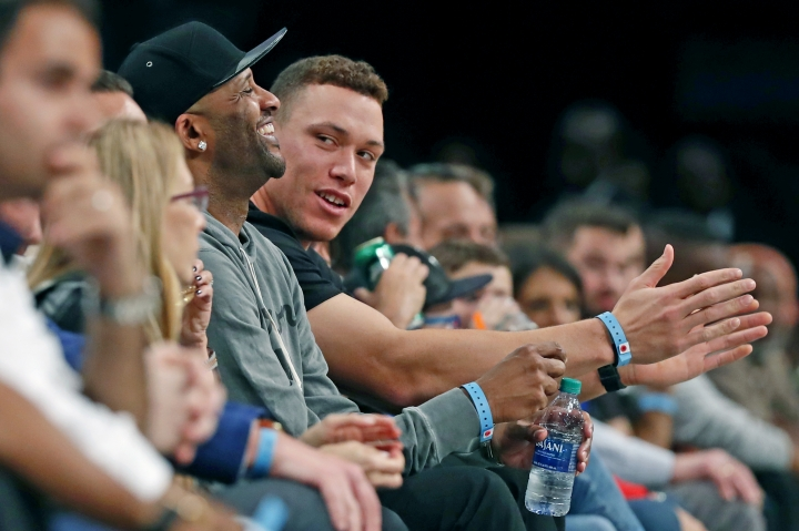 New York Yankees retired starting pitcher CC Sabathia, left, sits beside Yankees' Aaron Judge as the pair attend the first half of an NBA basketball game between the Brooklyn Nets and the New York Knicks, Friday, Oct. 25, 2019, in New York. (AP Photo/Kathy Willens)