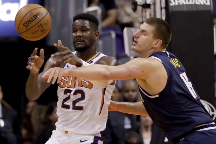 Phoenix Suns center Deandre Ayton (22) dishes off as Denver Nuggets center Nikola Jokic defends during the first half of an NBA preseason basketball game, Monday, Oct. 14, 2019, in Phoenix. (AP Photo/Matt York)