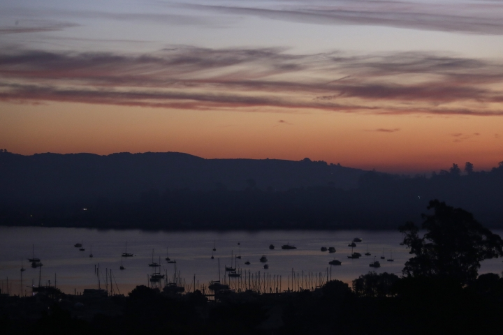 The Tiburon Peninsula remains dark from a power blackout Monday, Oct. 28, 2019, in this view from Sausalito, Calif. Millions of people in Northern California are on track to have lights come back on, but some may not be restored before another round of strong winds threaten to damage power lines and spark fires. Electricity is expected to begin being restored by Monday, though Pacific Gas & Electric Co. warned it might cut power again as soon as Tuesday with a forecast of strong winds expected to last until Wednesday. (AP Photo/Eric Risberg)