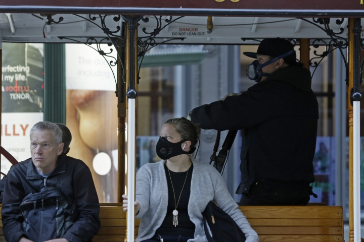 A California Street cable car operator and passenger wear breathing masks to protect against smoke from wildfires Monday, Oct. 28, 2019, in San Francisco. A wildfire that has been burning in Northern California's wine country since last week grew overnight as nearly 200,000 people remain under evacuation orders. (AP Photo/Eric Risberg)