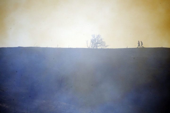 Firefighters walk on top of a burned down canyon caused by the Getty fire on Mandeville Canyon Monday, Oct. 28, 2019, in Los Angeles. (AP Photo/Marcio Jose Sanchez)
