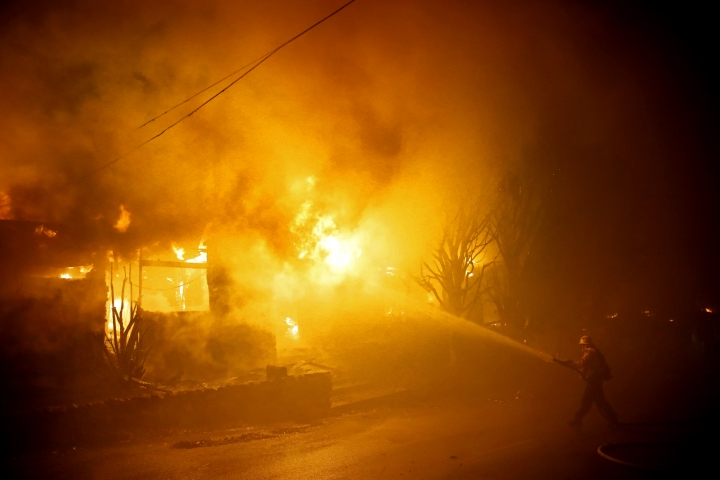 A firefighters tries to hose down flames as a home burns in the Getty fire area along Tigertail Road Monday, Oct. 28, 2019, in Los Angeles. (AP Photo/Marcio Jose Sanchez)
