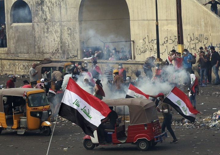 Iraq security forces fire tear gas to disperse anti-government protesters during a demonstration in Baghdad, Iraq, Monday, Oct. 28, 2019. Protests have resumed in Iraq after a wave of anti-government protests earlier this month were violently put down. (AP Photo/Hadi Mizban)