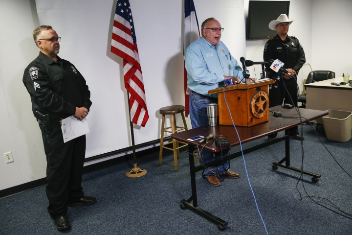 Hunt County Sheriff Randy Meeks, center, addresses members of the media at the sheriff's department headquarters after a deadly in Greenville, Texas, on Sunday, Oct. 27, 2019. A gunman opened fire at an off-campus Texas A&M University-Commerce party, which left over a dozen injured before he escaped in the ensuing chaos, a sheriff said Sunday. (Ryan Michalesko/The Dallas Morning News via AP)