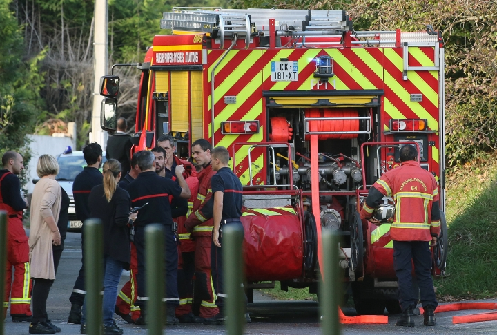 Local residents and firemen stand next to a fire truck after an incident at a mosque in Bayonne, southwestern France, Monday, Oct. 28, 2019. French authorities say a suspect has been arrested for allegedly shooting and seriously injuring two elderly men who caught him trying to set fire to a mosque's door. (AP Photo/Str)