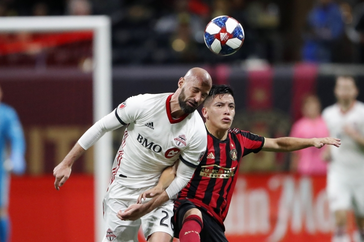Toronto FC defender Laurent Ciman (26) and Atlanta United midfielder Ezequiel Barco (8) vie for the ball during the second second half of the MLS soccer Eastern Conference final Wednesday, Oct. 30, 2019 in Atlanta. Toronto won 2-1 and advances to the MLS Cup title match, against the Seattle Sounders. (AP Photo/John Bazemore)
