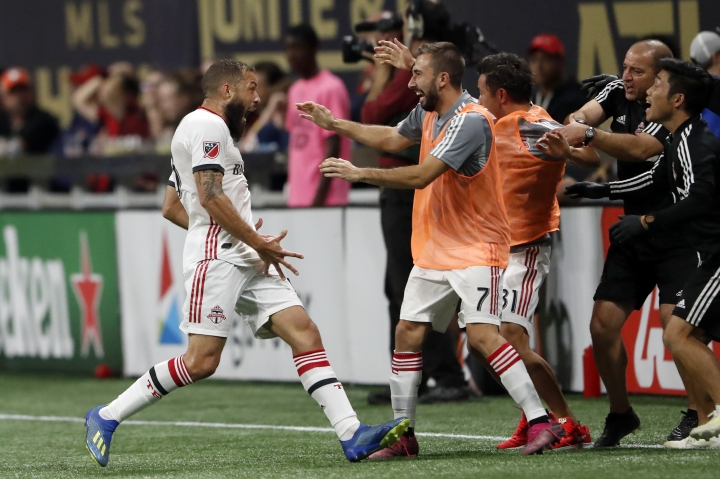 Toronto FC midfielder Nick DeLeon, left, celebrates with Nicolas Benezet (7) after scoring a goal during the second half of the MLS soccer Eastern Conference final against the Atlanta United on Wednesday, Oct. 30, 2019 in Atlanta. Toronto won 2-1. (AP Photo/John Bazemore)
