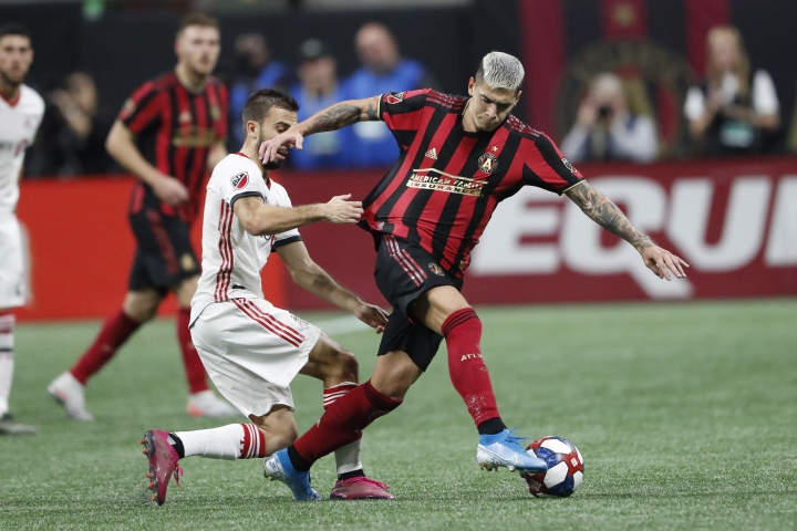 Atlanta United defender Franco Escobar (2) moves the ball as Toronto FC midfielder Nicolas Benezet (7) pulls on his jersey in the first half of their MLS Eastern Conference final soccer match Wednesday, Oct. 30, 2019 in Atlanta. (AP Photo/John Bazemore)