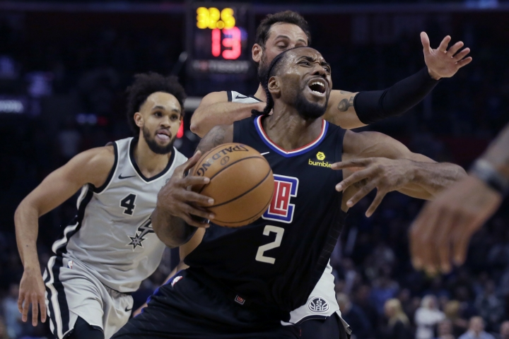 Los Angeles Clippers forward Kawhi Leonard drives to the basket past San Antonio Spurs guard Marco Belinelli, behind, of Italy, and guard Derrick White, left, during the second half of an NBA basketball game in Los Angeles, Thursday, Oct. 31, 2019. (AP Photo/Alex Gallardo)