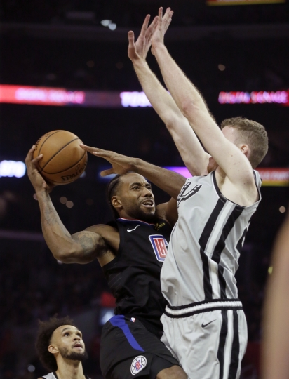 Los Angeles Clippers forward Kawhi Leonard, left, is defended by San Antonio Spurs center Jakob Poeltl during the second half of an NBA basketball game in Los Angeles, Thursday, Oct. 31, 2019. (AP Photo/Alex Gallardo)