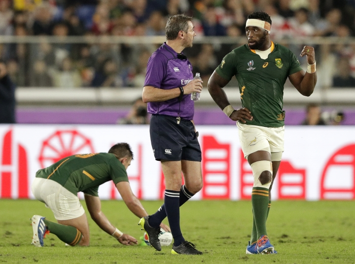 South Africa's Siya Kolisi, right, talks with Referee Jerome Garces, as South Africa's Handre Pollard prepares for a penalty kick during the Rugby World Cup semifinal at International Yokohama Stadium between Wales and South Africa in Yokohama, Japan, Sunday, Oct. 27, 2019. (AP Photo/Aaron Favila)