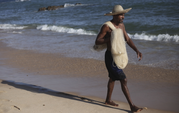 Arivaldo Sousa walks carrying a fishing net at Itapua beach in Salvador, Brazil, Saturday, Oct. 26, 2019. Sousa normally harvests 175 pounds (80 kilograms) of lobster per month but has fished a mere fraction of that recently, with hotels and restaurants no longer buying for fear of contamination from an oil spill in the region. (AP Photo/Raphael Muller)
