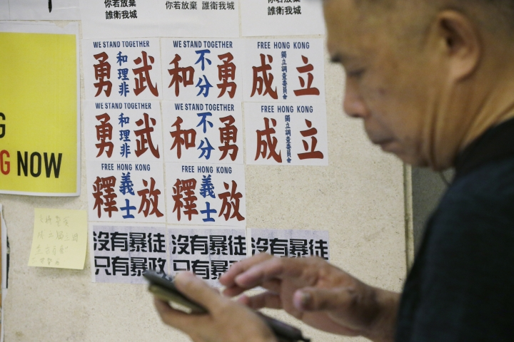 "A man walks past the posters with Chinese words read ""Peaceful protesters and frontliners stand together"" at a shopping mall in Hong Kong, Sunday, Nov. 3, 2019. (AP Photo/Dita Alangkara)"