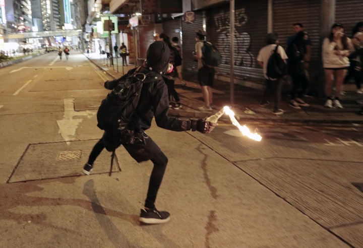 A protester prepares to hurl a molotov cocktail toward police during clashes in Hong Kong, Saturday, Nov. 2, 2019. Riot police fired multiple rounds of tear gas and used water cannons Saturday to swiftly break up a rally in downtown Hong Kong by thousands of masked protesters demanding meaningful autonomy after Beijing indicated it could tighten its grip on the Chinese territory. (AP Photo/Dita Alangkara)