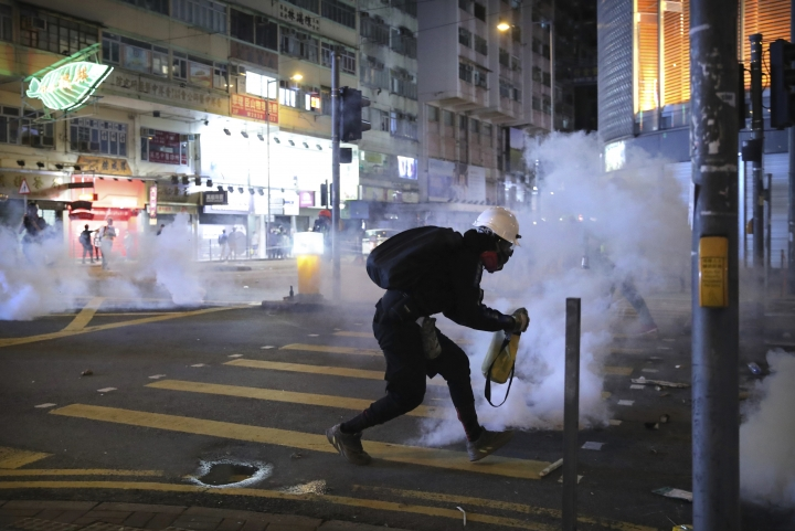 A demonstrator reacts as police fire tear gas during a protest in Hong Kong, Saturday, Nov. 2, 2019. Pro-democracy protesters attacked the office of Chinese news agency Xinhua for the first time Saturday, after familiar chaos downtown that saw police and demonstrators trading petrol bombs, tear gas and water cannon in the 22nd straight weekend of unrest. (AP Photo/Kin Cheung)