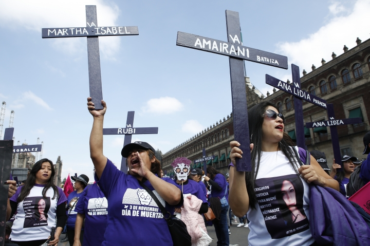 Demonstrators shout with crosses during a protest demanding justice for women who have been murdered or disappeared, one day after the Day of the Dead holiday in Mexico City, Sunday, Nov. 3, 2019. Nine women are killed per day in Mexico, according to the U.N. (AP Photo/Ginnette Riquelme)
