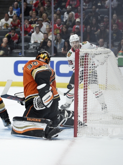 Chicago Blackhawks right wing Alex DeBrincat, right, scores a goal against Anaheim Ducks goalie Ryan Miller (30) during the first period of an NHL hockey game in Anaheim, Calif., Sunday, Nov. 3, 2019. (AP Photo/Kelvin Kuo)