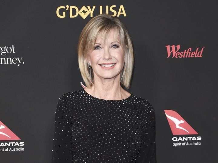 "FILE - In this Jan. 27, 2018 file photo, Olivia Newton-John attends the 2018 G'Day USA Los Angeles Gala at the InterContinental Hotel Los Angeles. Two collectors said you're the one that I want to Newton-John's iconic ""Grease"" leather jacket and skintight pants at an auction in Beverly Hills, Saturday, Nov. 2, 2019. Julien's Auctions says the combined ensemble, which Newton-John's character Sandy wears in the closing number of the 1978 film, fetched $405,700 total. The leather jacket sold for $243,200 and the pants, which Newton-John famously had to be sewn into, went for $162,500. (Photo by Richard Shotwell/Invision/AP, File)"