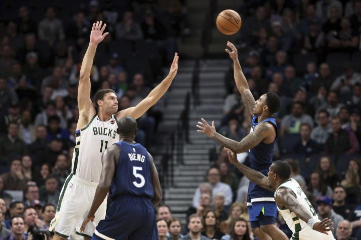 Minnesota Timberwolves' Jeff Teague, right, shoots over Milwaukee Bucks' Brook Lopez in the first half of an NBA basketball game Monday, Nov 4, 2019, in Minneapolis. (AP Photo/Jim Mone)