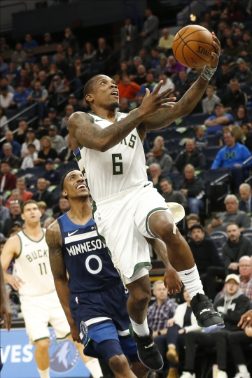 Milwaukee Bucks' Eric Bledsoe, right, lays up a shot as Minnesota Timberwolves' Jeff Teague looks on in the first half of an NBA basketball game Monday, Nov 4, 2019, in Minneapolis. (AP Photo/Jim Mone)