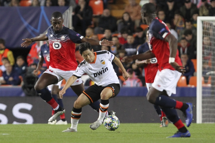 Valencia's Lee Kang-in, center, vies for the ball with Lille's Boubakary Soumare, left, during the Champions League group H soccer match between Valencia and Lille at the Mestalla stadium in Valencia, Spain, Tuesday, Nov. 5, 2019. (AP Photo/Alberto Saiz)