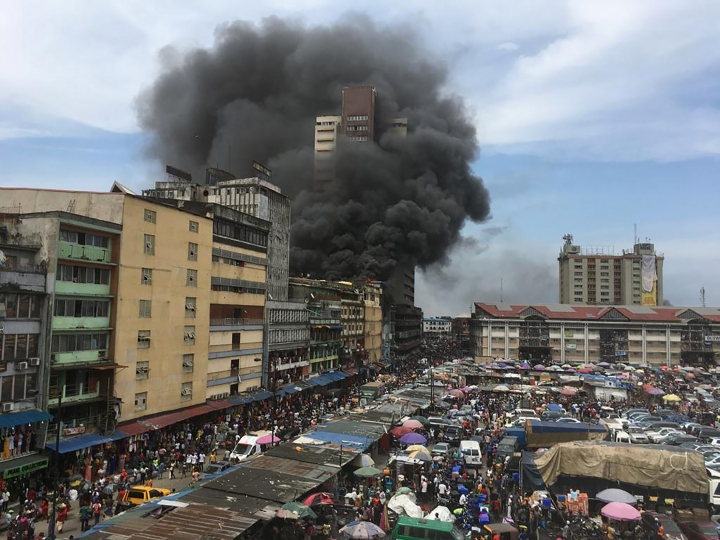 Smoke rises from a fire in downtown Lagos, Nigeria, Tuesday, Nov. 5, 2019. Nigerian firefighters are trying to extinguish a fire at the Balogun market in central Lagos. Thick black smoke and flames are shooting from five-story buildings surrounding the market as fire trucks attempt to get access to the fire. (AP Photo/Sunday Alamba)