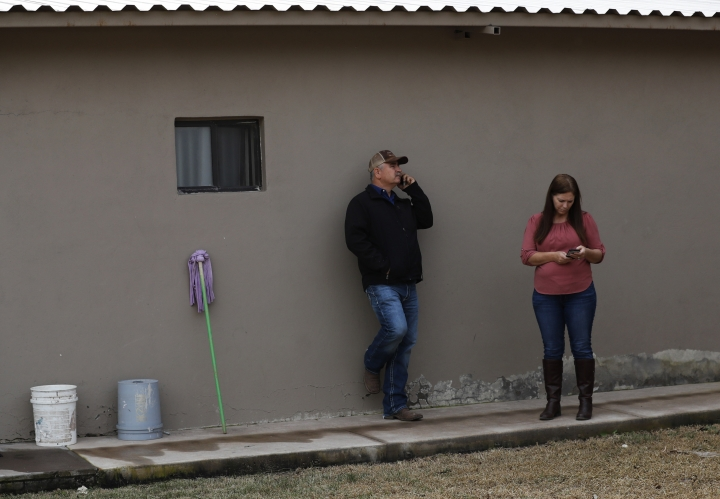 William Stubbs and Elsie Liddiard call friends and members of the extended LeBaron family as they and others organize themselves to drive in a group to the site of an attack on members of the LeBaron family, in the Colonia LeBaron in Chihuahua state in northern Mexico, Wednesday, Nov. 6, 2019. Three women and six of their children, related to the extended LeBaron family, were gunned down in an attack while traveling along Mexico's Chihuahua and Sonora state border on Nov. 4. Stubbs is a friend of the family while Liddiard is related to one of the victims. (AP Photo/Marco Ugarte)