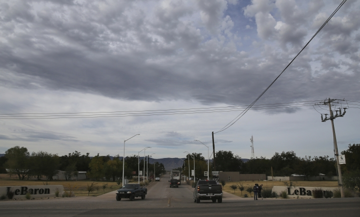 Trucks move past signs that announce the Colonia LeBaron, a community settled by members of the extended LeBaron family in Chihuahua state in northern Mexico, Wednesday, Nov. 6, 2019. The three women and six of their children who were gunned down in a Nov. 4 attack while traveling along Mexico's Chihuahua and Sonora state border, were apparently related to the extended LeBaron family, whose members have run afoul of the drug traffickers over the years. (AP Photo/Marco Ugarte)