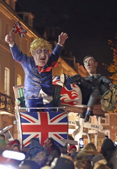 An effigy of Britain's Prime Minister Boris Johnson, left, and Leader of the House of Commons Jacob Rees-Mogg, during the annual bonfire night procession in the town of Lewes, Britain, Tuesday Nov. 5, 2019. The annual event traditionally includes high-profile political characters, with Britain's Brexit split with Europe being one of the main issues as the country goes to the polls in a General Election on Dec. 12. (Gareth Fuller/PA via AP)