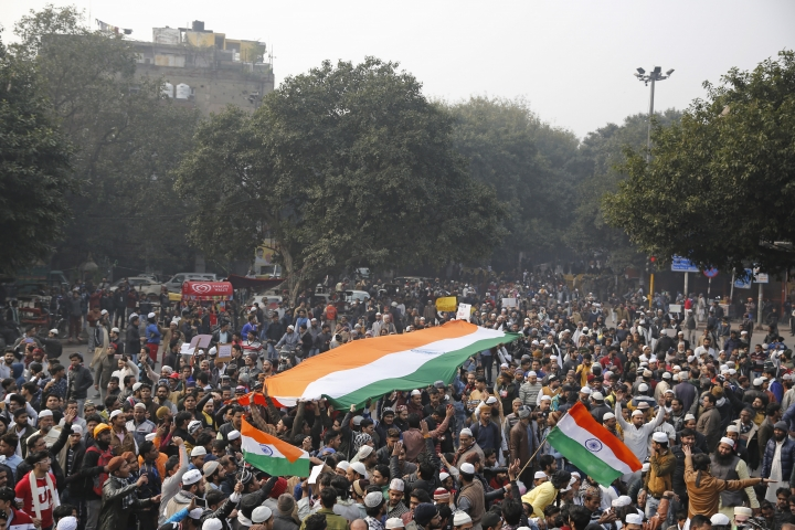 Indians carry national flags as they march during a protest against the Citizenship Amendment Act after Friday prayers outside Jama Masjid in New Delhi, India, Friday, Dec. 20, 2019. Police banned public gatherings in parts of the Indian capital and other cities for a third day Friday and cut internet services to try to stop growing protests against a new citizenship law that have so far left eight people dead and more than 1,200 others detained. (AP Photo/Altaf Qadri)