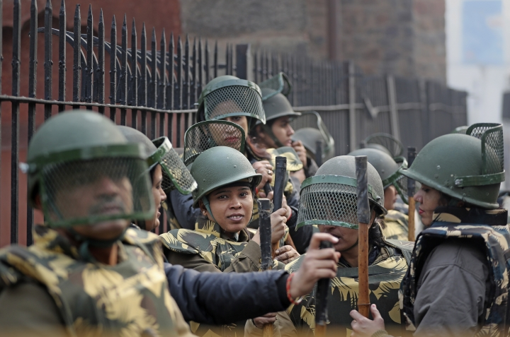 Indian police personnel stand guard at a barricade as Indians protest against the Citizenship Amendment Act in New Delhi, India, Friday, Dec. 20, 2019. Police banned public gatherings in parts of the Indian capital and other cities for a third day Friday and cut internet services to try to stop growing protests against a new citizenship law that have left eight people dead and more than 4,000 others detained. (AP Photo/Altaf Qadri)