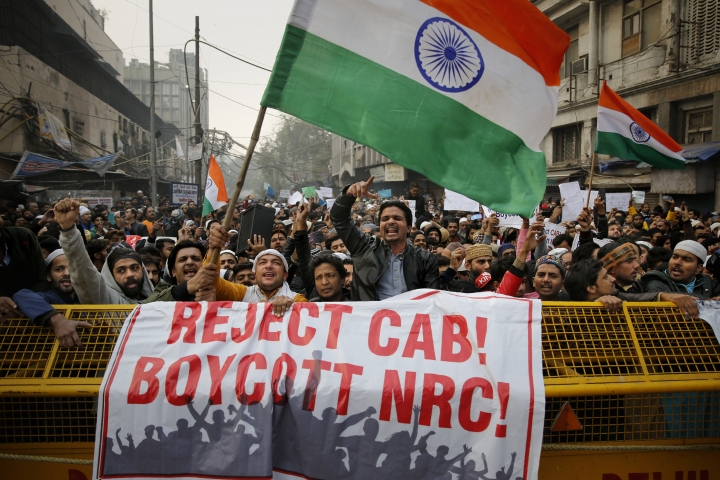 Indians hold placards as national flags and shout slogans behind a police barricade during a protest against the Citizenship Amendment Act in New Delhi, India, Friday, Dec. 20, 2019. Police banned public gatherings in parts of the Indian capital and other cities for a third day Friday and cut internet services to try to stop growing protests against a new citizenship law that have so far left eight people dead and more than 1,200 others detained. (AP Photo/Altaf Qadri)