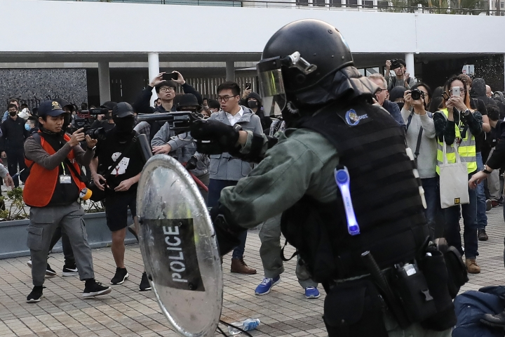 A riot policeman points his gun during a rally to show support for Uighurs and their fight for human rights in Hong Kong, Sunday, Dec. 22, 2019. (AP Photo/Lee Jin-man)