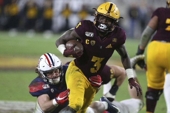 Arizona State's Eno Benjamin (3) slips the tackle of Arizona's Colin Schooler (7) during the second half of an NCAA college football game Saturday, Nov. 30, 2019, in Tempe, Ariz. (AP Photo/Darryl Webb)