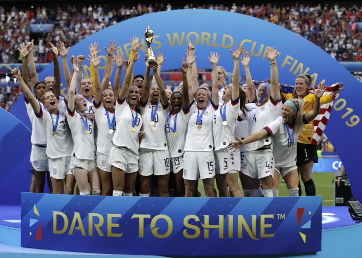 "File-This July 7, 2019, file photo shows the United States' team celebrating with the trophy after winning the Women's World Cup final soccer match between US and The Netherlands at the Stade de Lyon in Decines, outside Lyon, France. Rapinoe, World Cup, USA. Stadium bellows: ""Equal pay!""(AP Photo/Alessandra Tarantino, File)"