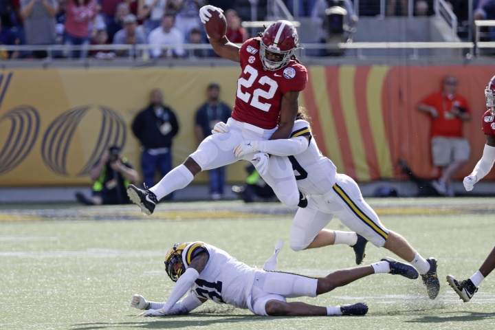 Alabama running back Najee Harris (22) gains yardage as he tries to get past Michigan defensive back Vincent Gray (31) and defensive back DeMarcco Hellams, right, during the first half of the Citrus Bowl NCAA college football game, Wednesday, Jan. 1, 2020, in Orlando, Fla. (AP Photo/John Raoux)