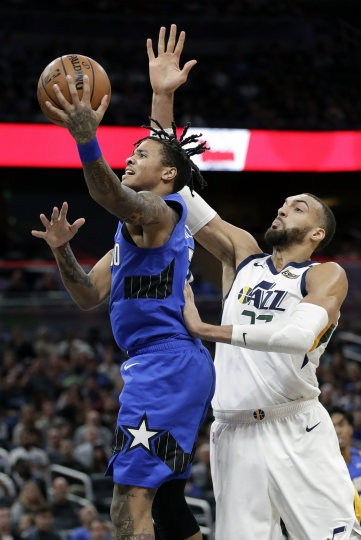 Orlando Magic guard Markelle Fultz, left, makes a shot in front of Utah Jazz center Rudy Gobert during the first half of an NBA basketball game, Saturday, Jan. 4, 2020, in Orlando, Fla. (AP Photo/John Raoux)