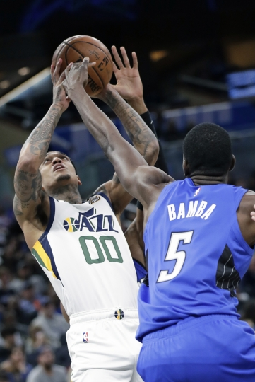 Utah Jazz guard Jordan Clarkson (00) tries to get off a shot over Orlando Magic center Mo Bamba (5) during the second half of an NBA basketball game, Saturday, Jan. 4, 2020, in Orlando, Fla. (AP Photo/John Raoux)