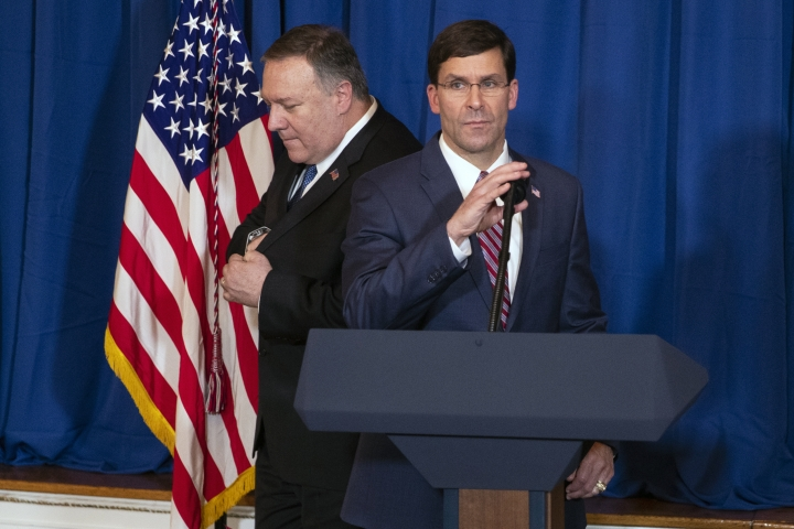 Secretary of State Mike Pompeo, left, hands off the microphone to Secretary of Defense Mark Esper to deliver a statement on Iraq and Syria, at President Donald Trump's Mar-a-Lago property, Sunday, Dec. 29, 2019, in Palm Beach, Fla. (AP Photo/ Evan Vucci)