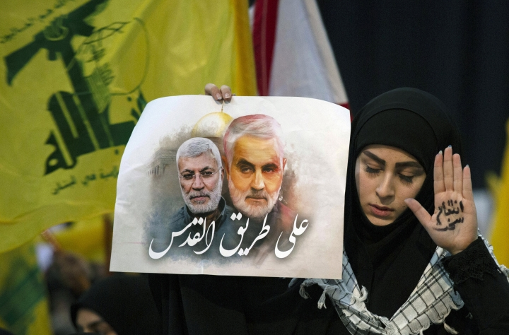 "A supporter of Hezbollah leader Sayyed Hassan Nasrallah wears the words ""powerful revenge"" on her hand, ahead of the leader's televised speech in a southern suburb of Beirut, Lebanon, Sunday, Jan. 5, 2020 following the U.S. airstrike in Iraq that killed Iranian Revolutionary Guard Gen. Qassem Soleimani. The placard in her other hand depicts Soleimaini and Iraq's Popular Mobilization forces commander Abu Mahdi al-Muhandis, who was also killed in the strike. Arabic on placard reads: ""On the road to Jerusalem."" (AP Photo/Maya Alleruzzo)"