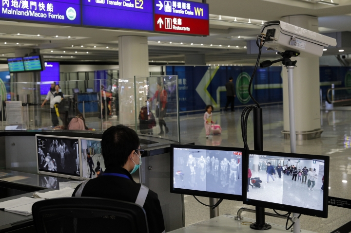 FILE - In this Jan. 4, 2020, file photo, a health surveillance officer monitors passengers arriving at the Hong Kong International airport in Hong Kong. A preliminary investigation into viral pneumonia illnesses sickening dozens of people in and around China has identified the possible cause as a new type of coronavirus, state media said Thursday, Jan. 9, 2020. In Hong Kong, 15 patients with symptoms of respiratory illness were being treated as of Sunday. (AP Photo/Andy Wong, File)