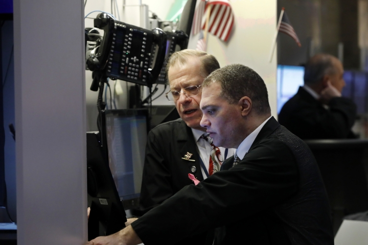 A pair of traders confer on the floor of the New York Stock Exchange, Thursday, Jan. 9, 2020. Stocks are opening broadly higher on Wall Street as traders welcome news that China's top trade official will head to Washington next week to sign a preliminary trade deal with the U.S. (AP Photo/Richard Drew)
