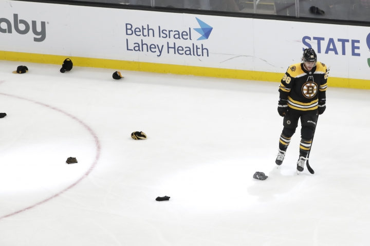Boston Bruins right wing David Pastrnak skates near hats on the ice after his goal against the Winnipeg Jets in the third period of an NHL hockey game, Thursday, Jan. 9, 2020, in Boston. It was his third goal of the night. (AP Photo/Elise Amendola)