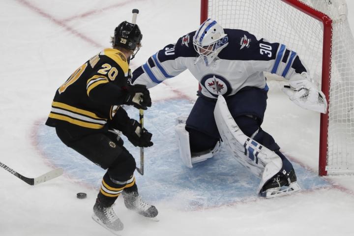 Boston Bruins center Joakim Nordstrom (20) can't score on his bid against Winnipeg Jets goaltender Laurent Brossoit (30) during the first period of an NHL hockey game Thursday, Jan. 9, 2020, in Boston. (AP Photo/Elise Amendola)