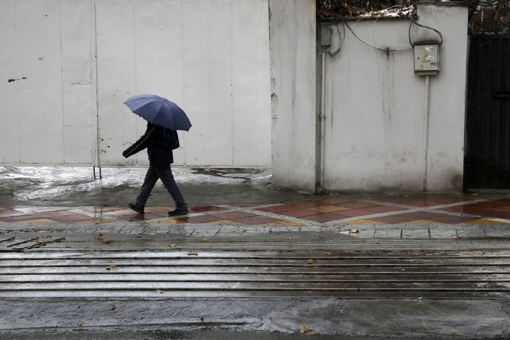 A man shelters from the snow with an umbrella as he walks on a sidewalk in northern Tehran, Iran, Thursday, Jan. 9, 2020. Many Iranians say they are relieved that neither their country nor the United States appear primed right now for a more direct military confrontation that could lead to war. (AP Photo/Vahid Salemi)