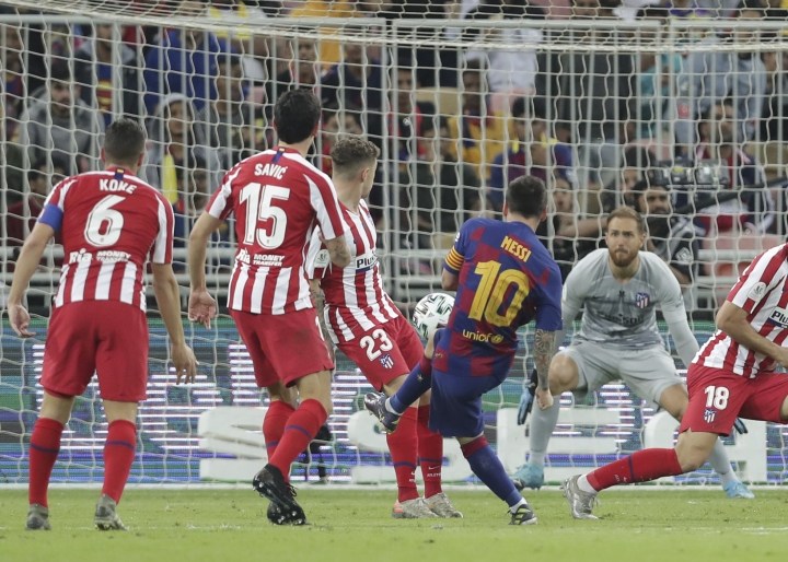 Barcelona's Lionel Messi scores his side first goal during the Spanish Super Cup semifinal soccer match between Barcelona and Atletico Madrid at King Abdullah stadium in Jiddah, Saudi Arabia, Thursday, Jan. 9, 2020. (AP Photo/Hassan Ammar)