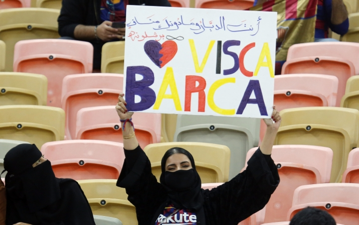 A Barcelona fan holds a banner ahead of the Spanish Super Cup semifinal soccer match between Barcelona and Atletico Madrid at King Abdullah stadium in Jiddah, Saudi Arabia, Thursday, Jan. 9, 2020. (AP Photo/Amr Nabil)