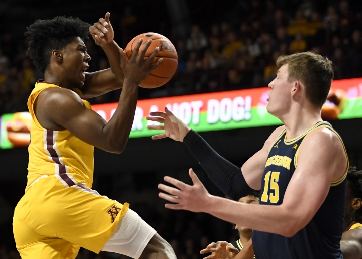 Minnesota's Marcus Carr, left, loses the ball against Michigan's Jon Teske (15) in the first half during an NCAA college basketball game on Sunday, Jan. 12, 2020, in Minneapolis. (AP Photo/Hannah Foslien)